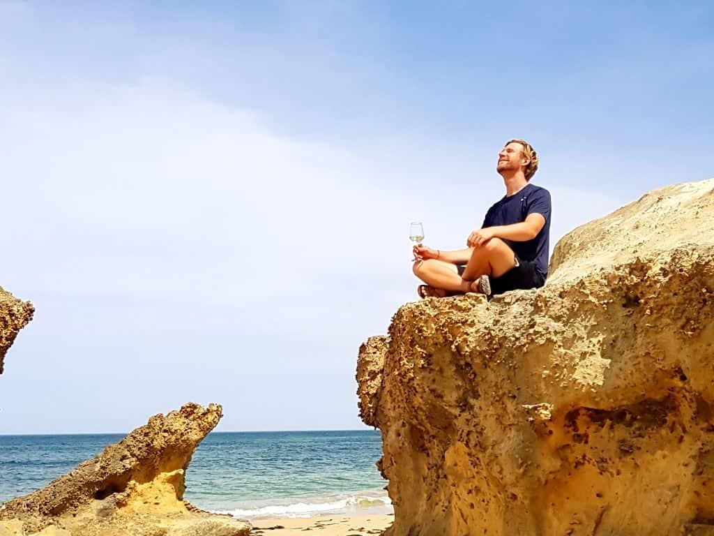 great ocean road jost bettinga sitzt auf stein mit weinglas